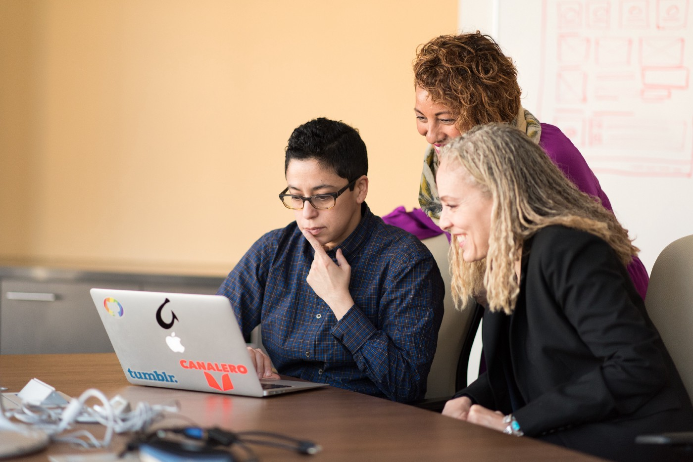 three employees collaborate around a laptop computer sitting on a table