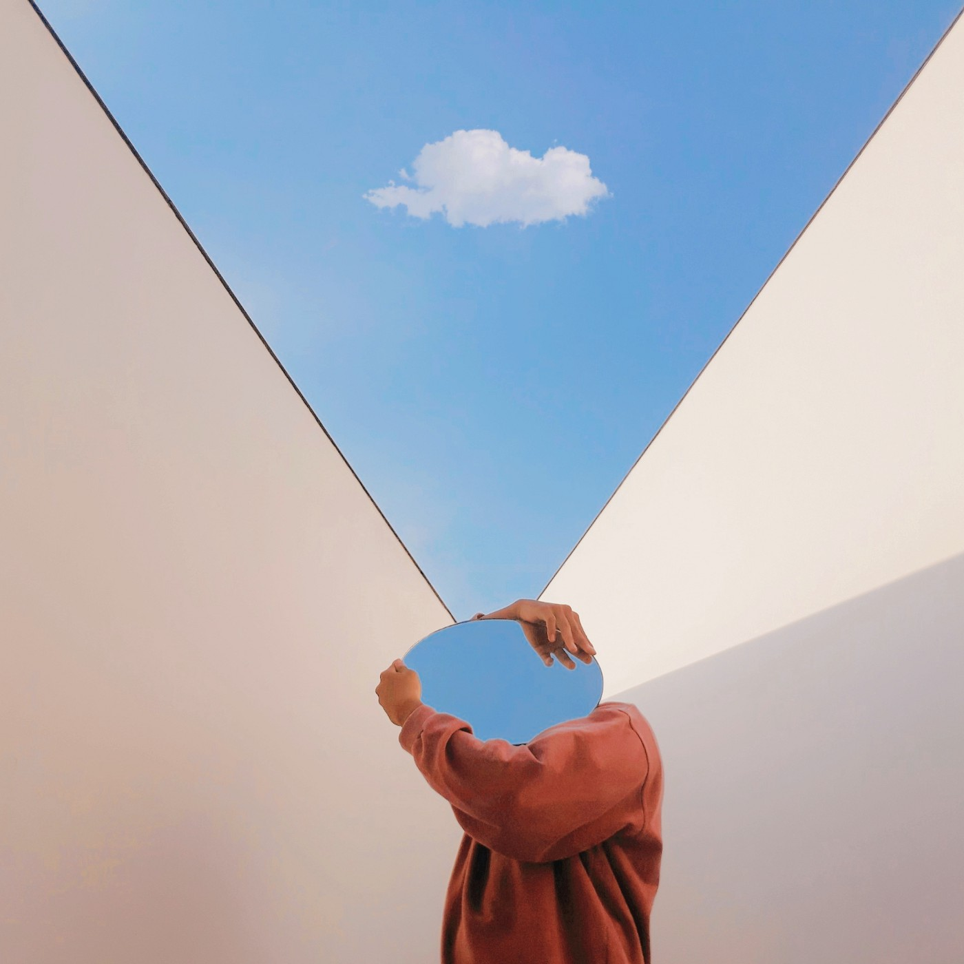 A photo of a person holding a mirror that reflects the blue sky. The mirror is covering their face.