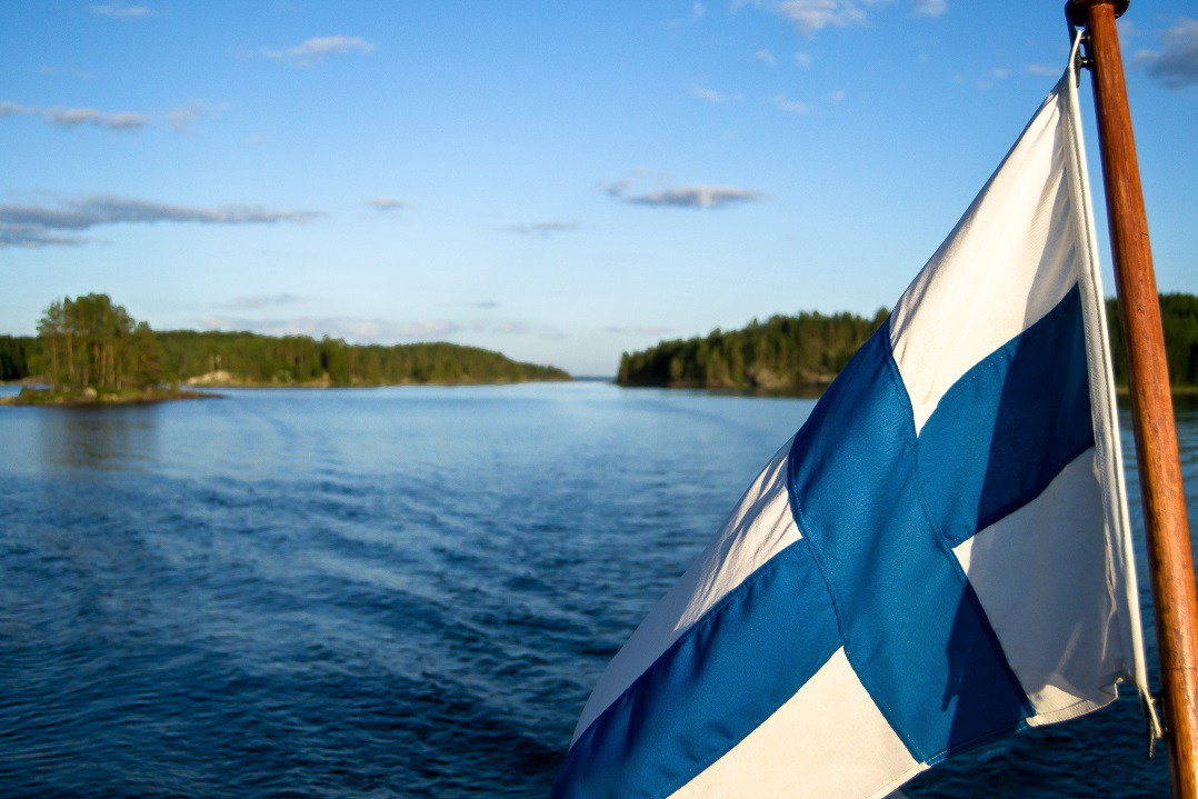 Finnish flag with idyllic lake Saimaa in the background