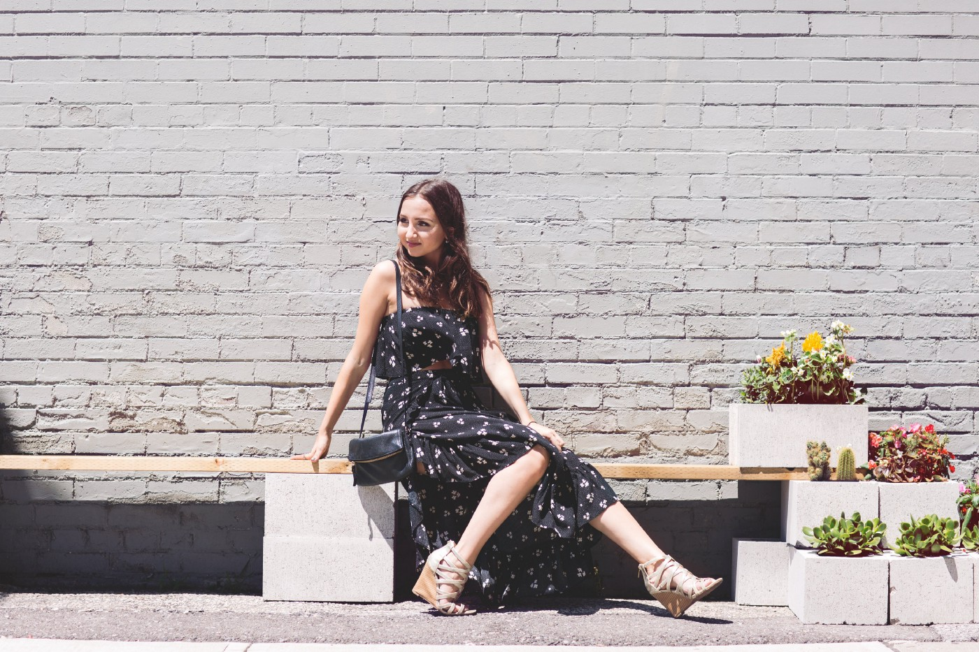 A woman in a floral dress smiles while sitting on a bench.
