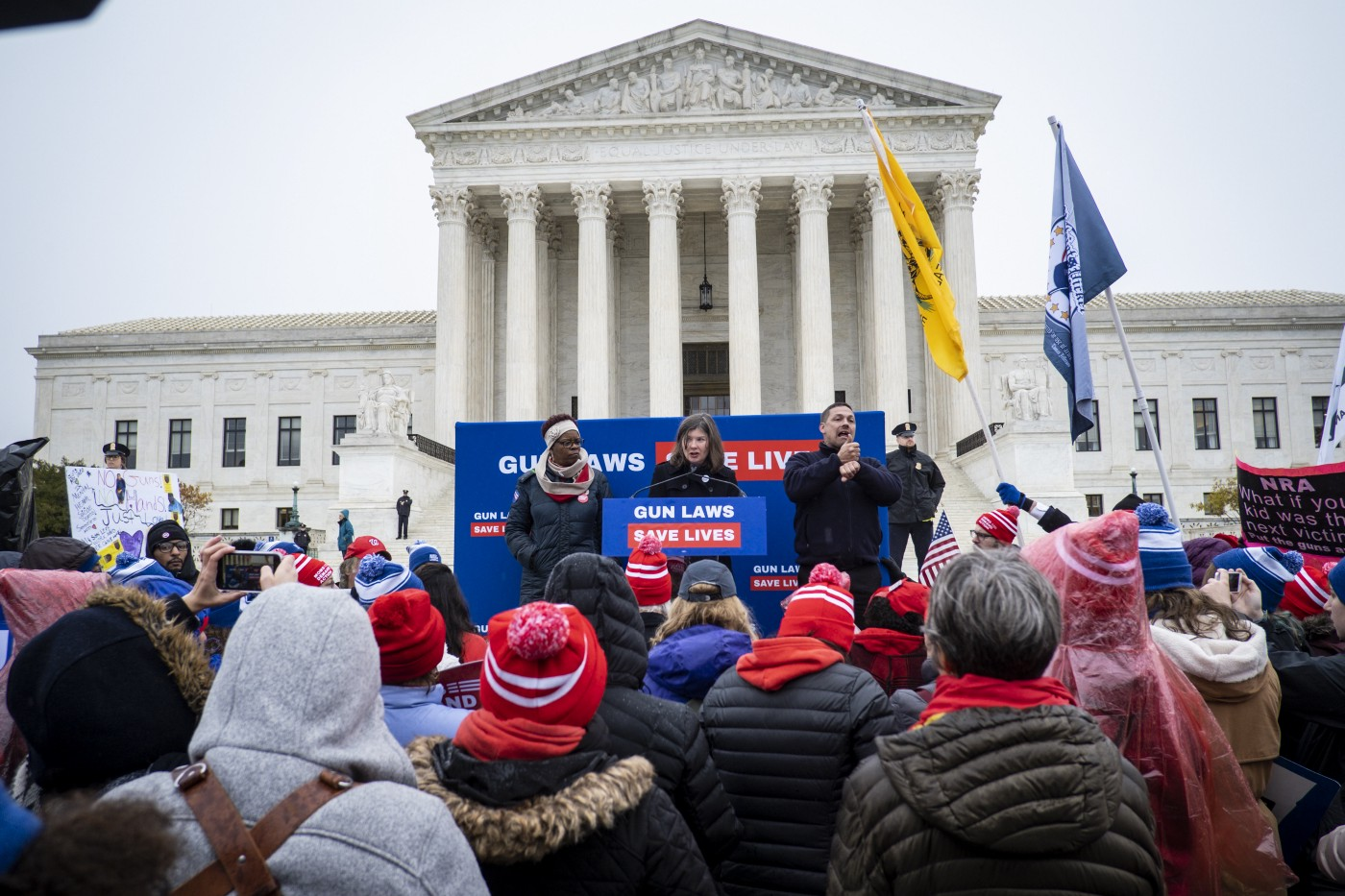 """A crowd gathers in front of the Supreme Court for a rally. Signs and banners say, """"gun laws save lives"""""""