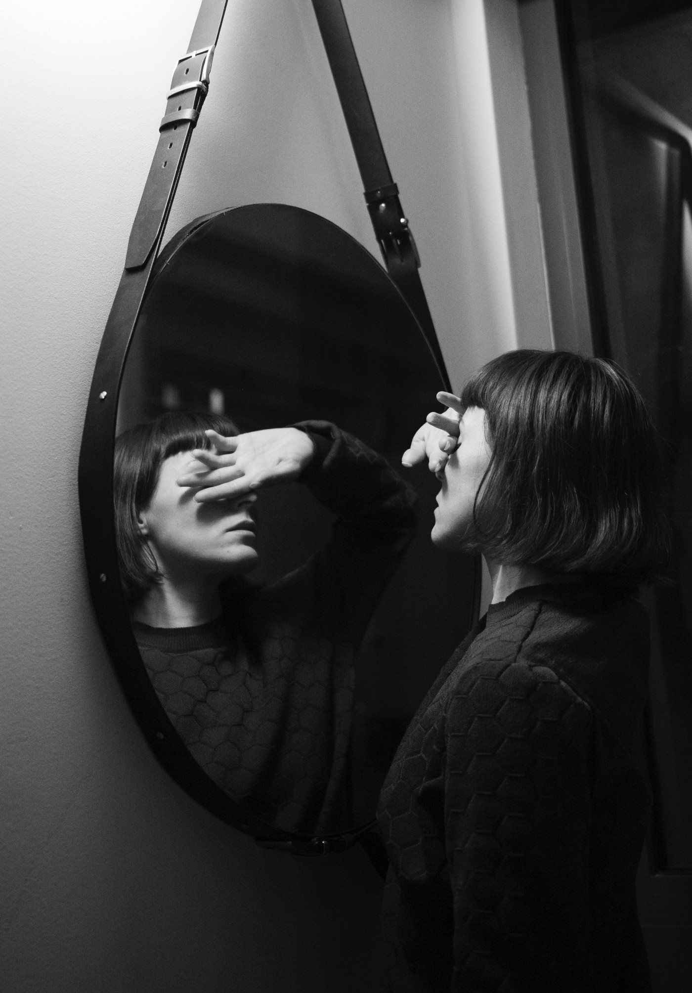 A black and white photo of a woman standing in front of a mirror resting the back of her hand across her eyes