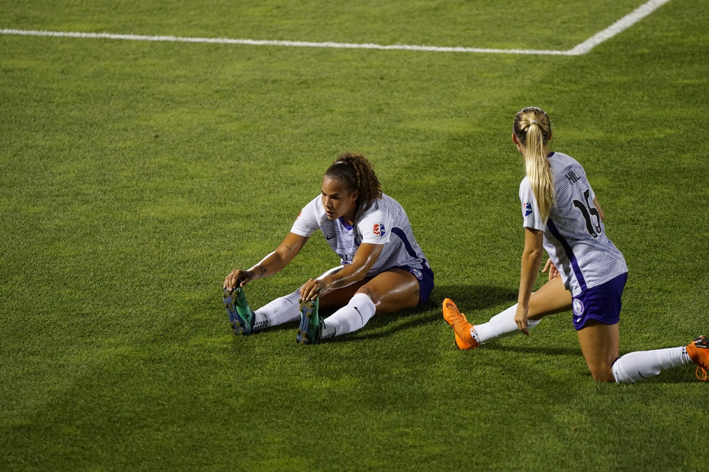 Two soccer players on the field doing preparatory stretches before the match