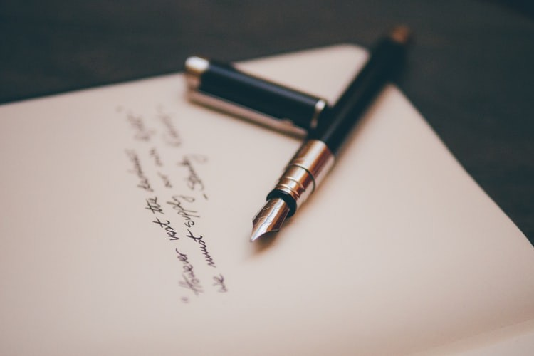 An image of a pen lying on a piece of paper on which is written the beginnings of a poem.