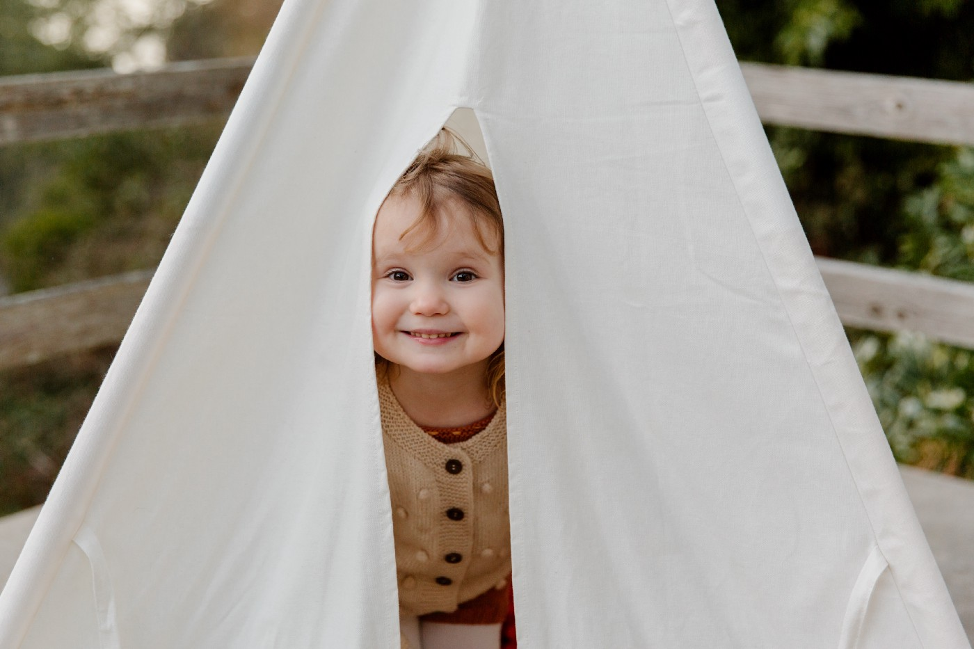 An angelic smiling baby girl peeking out naughtily from under a small white tent.