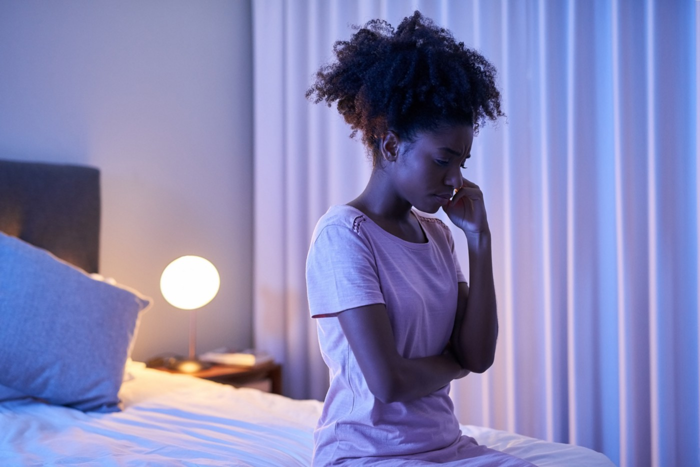 A troubled black woman sits at the edge of her bed.