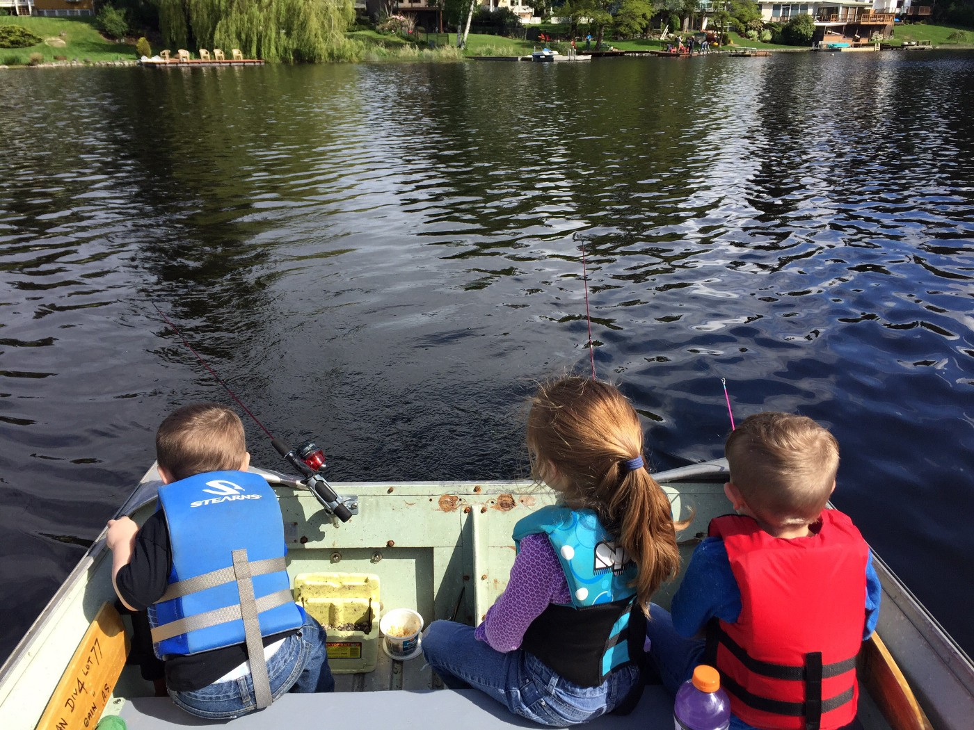 Three children fish in a lake from the back of a boat.