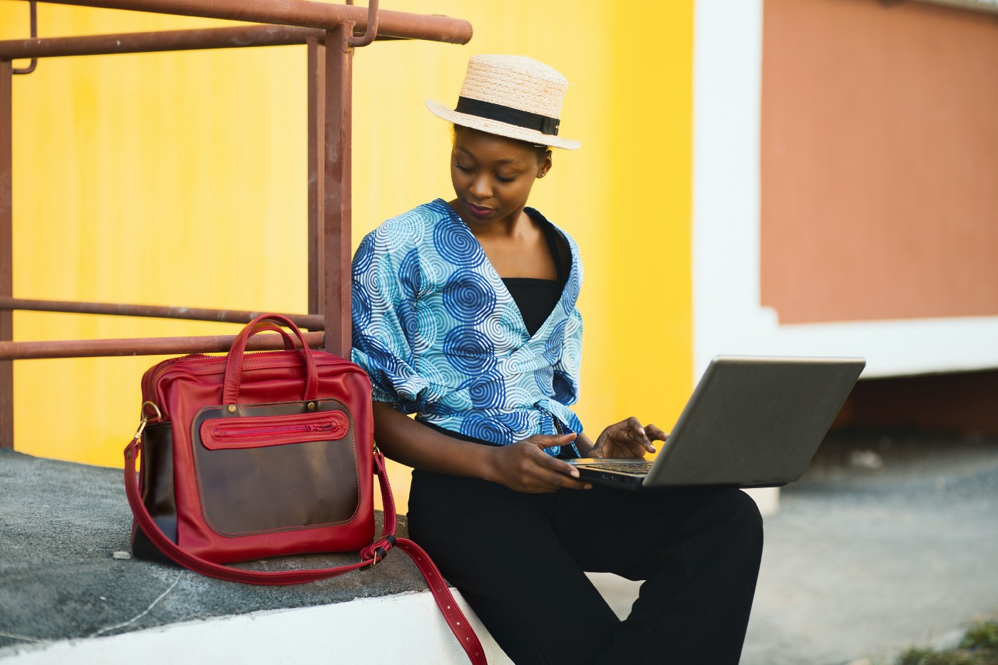 Woman sitting in front of a yellow wall beside a red bag while using a laptop