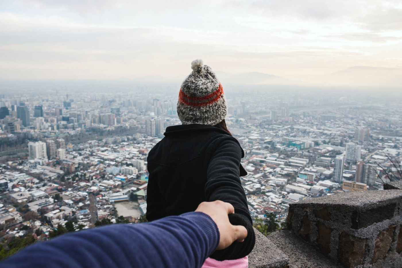 A woman facing forward reaches her arm back, guiding her companion to a viewpoint of the vast city in front of them.
