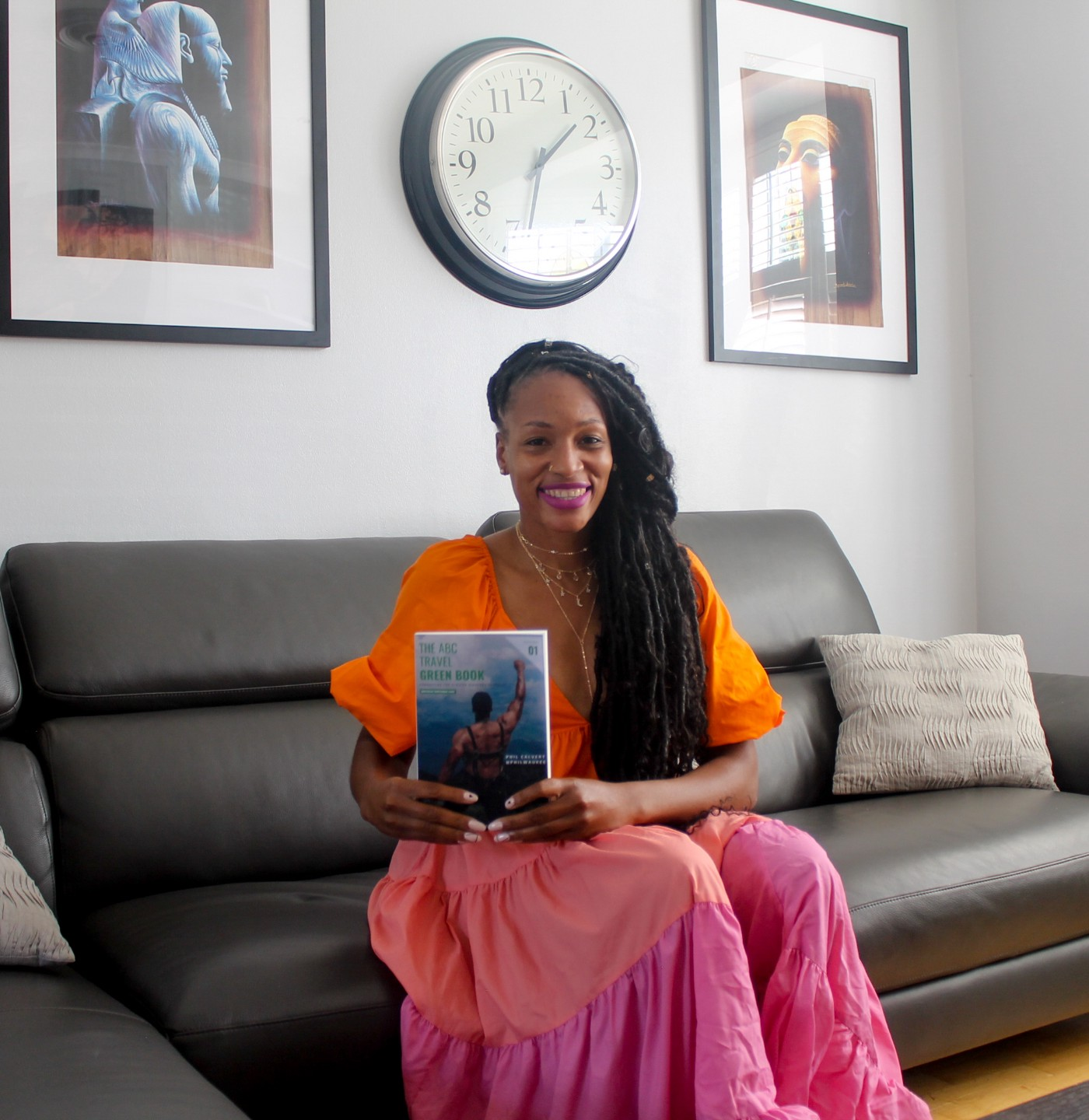 Martinique Lewis sitting on a black couch holding her book on her lap.