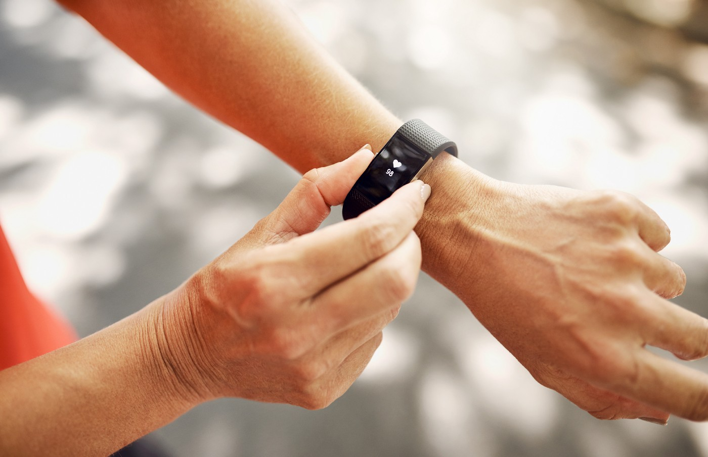 A close up of a person checking a wearable fitness tracker on their wrist.