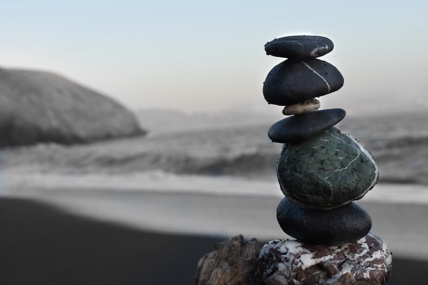 Six rocks balanced perfectly on top of each other by the sea.