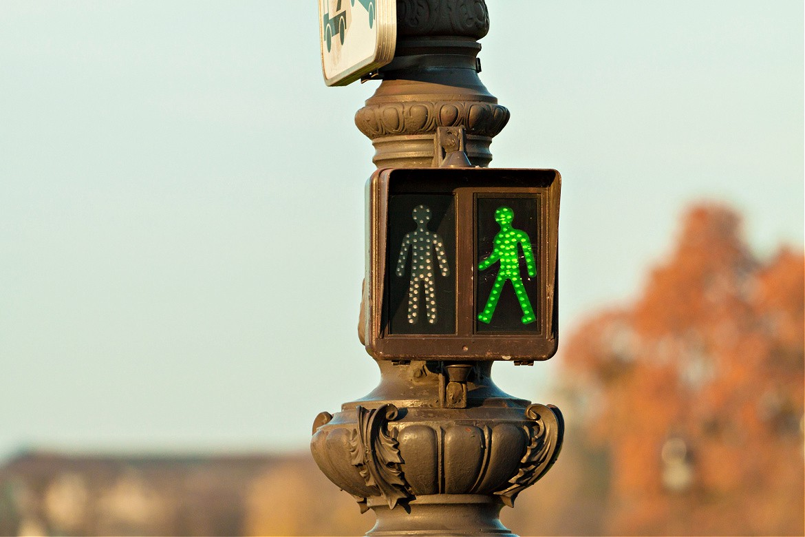 Green light image of a person walking on a traffic post