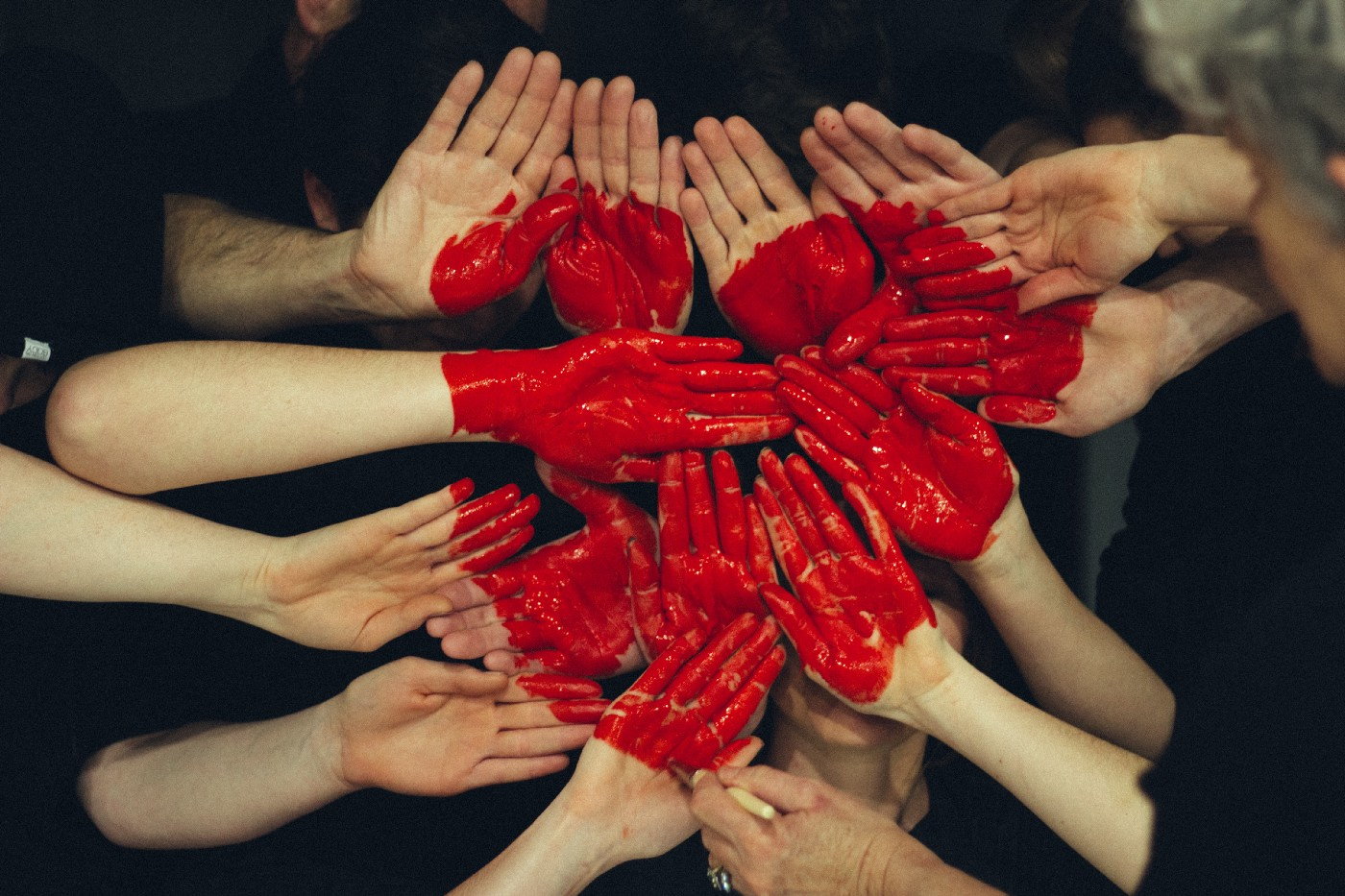 Hands coming together to form a heart with red paint. Photo credit goes to Tim Marshall.