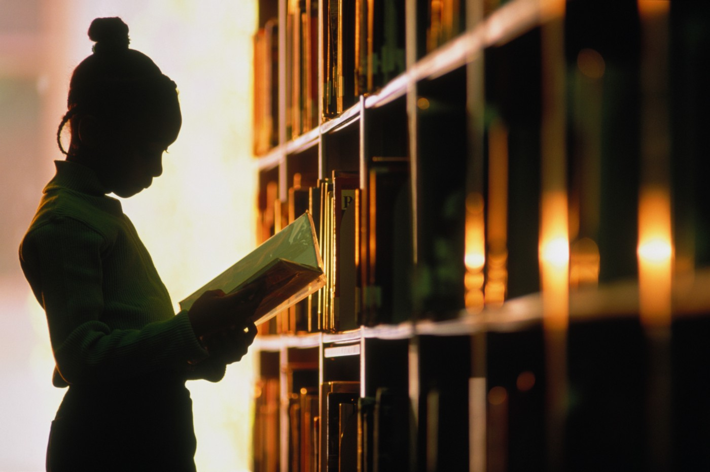 Young Black girl reads a book in school library.