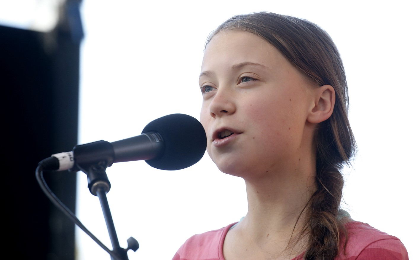 Activist Greta Thunberg speaking into a microphone as she leads the Youth Climate Strike.