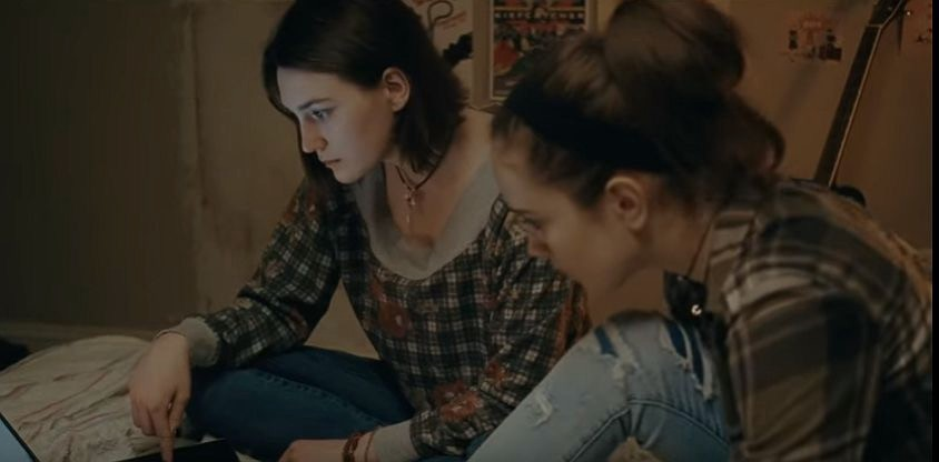 Autumn (Sidney Flanigan: left) and Skylar (Talia Ryder: right) sit on a bed, concernedly finding bus tickets on a laptop.