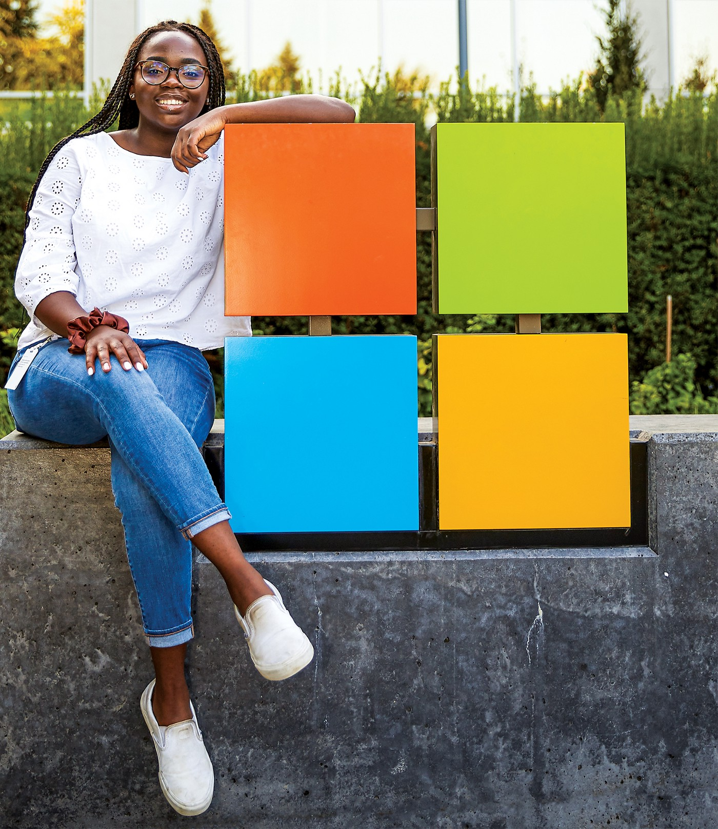 A young woman sits next to the iconic Microsoft logo and symbol.