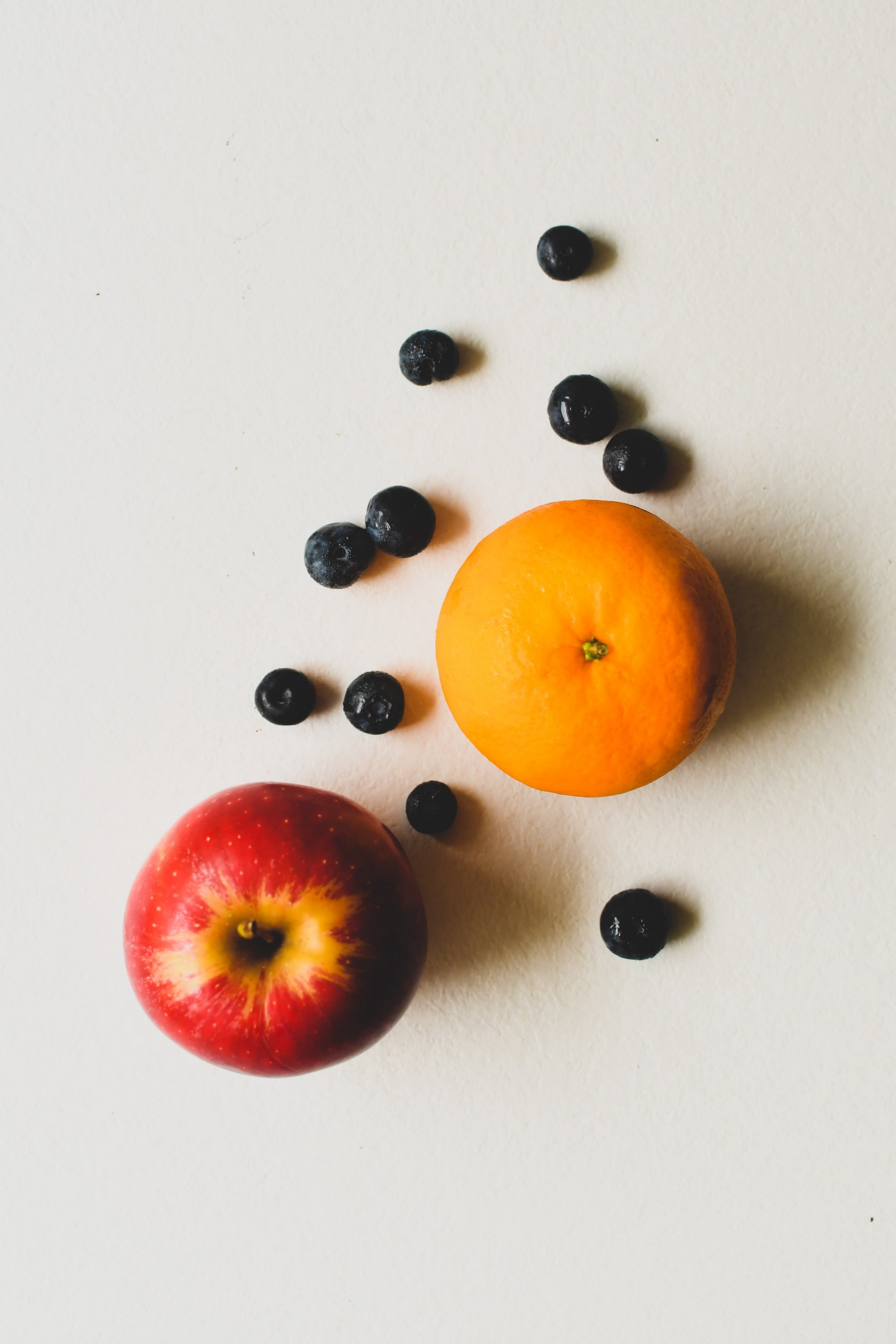 One apple, one orange, and a handful of blueberries