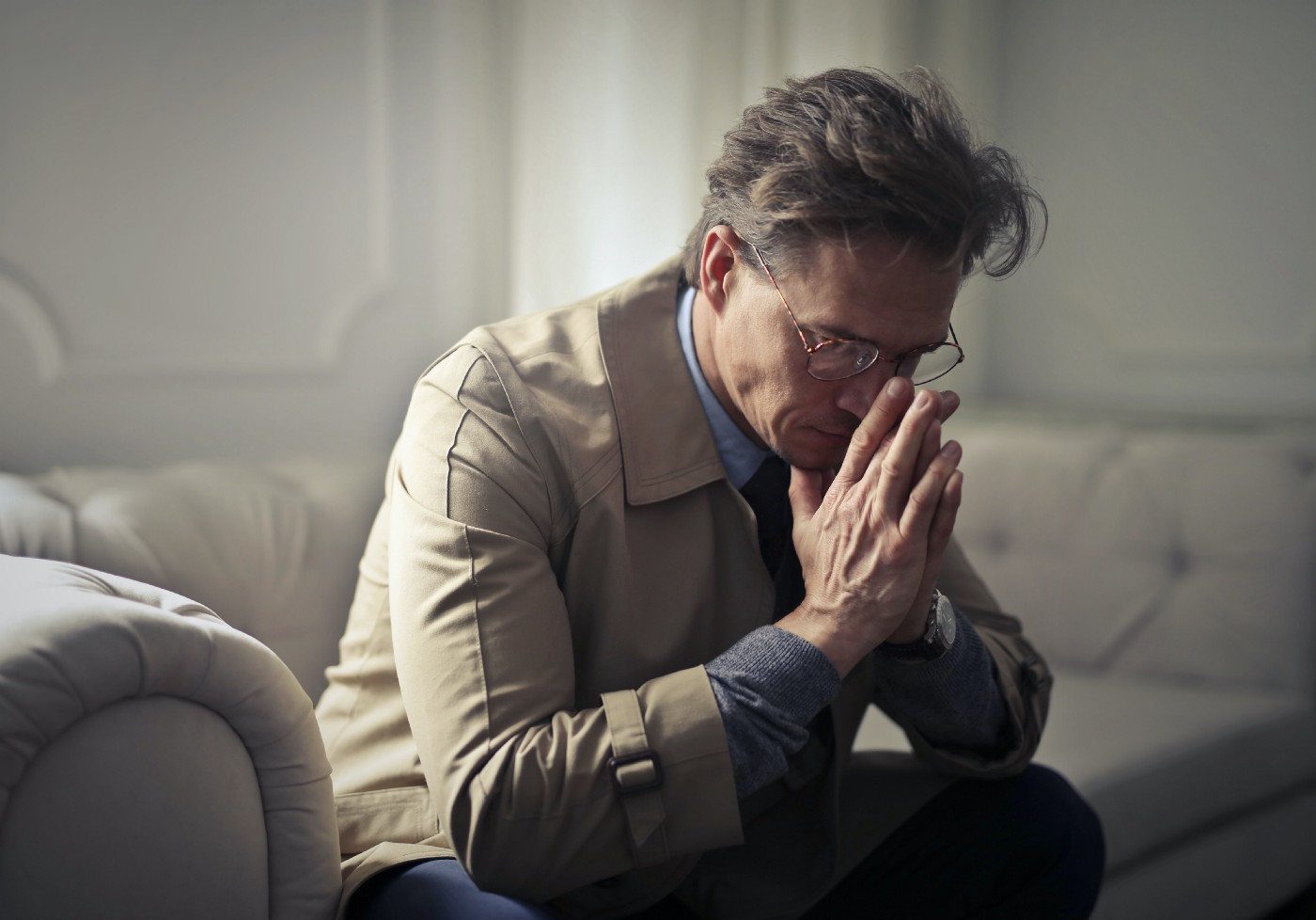 Sad mature businessman thinking about problems in living room