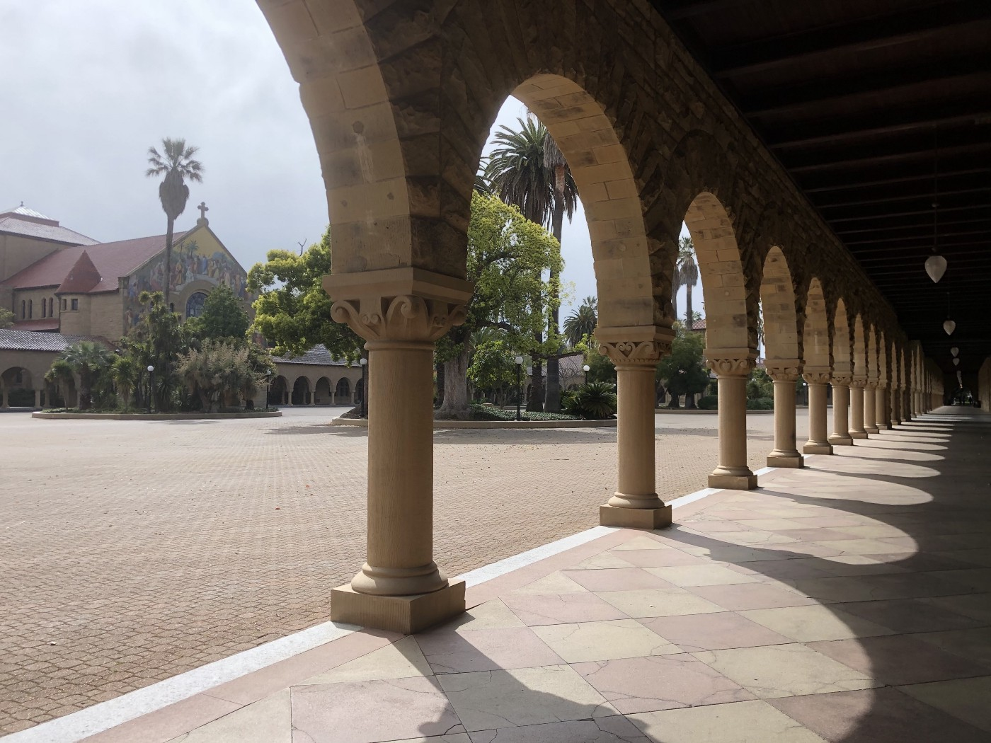 Picture of a covered stone walkway, with a long series of stone archways and pillars.