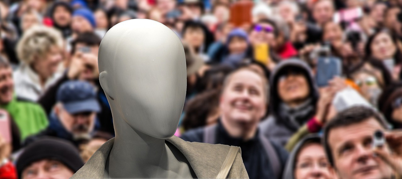A faceless image in the midst of a crowd of people