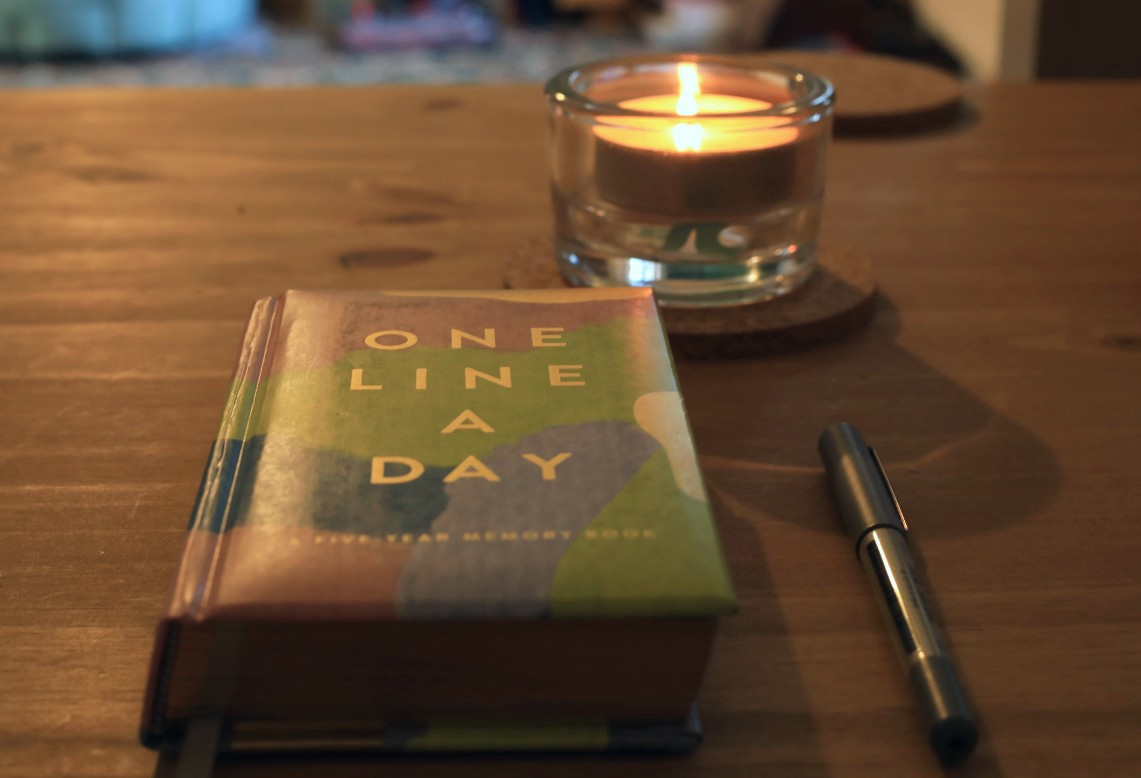 One Line a Day journal, a pen and a candle