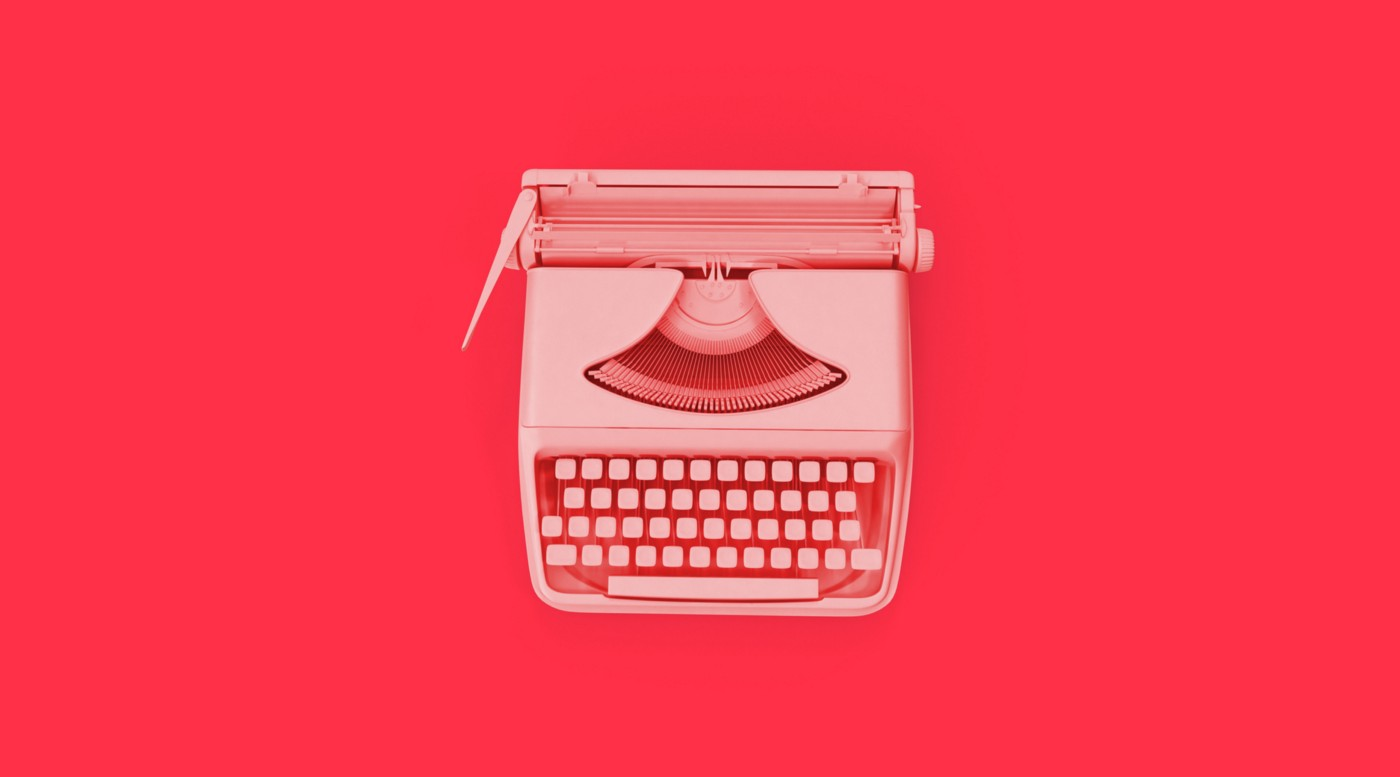 A photo of a typewriter against a red background.