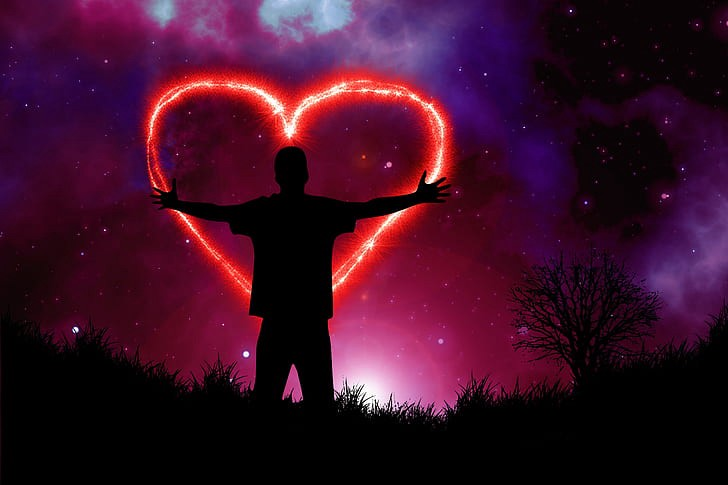Silhouette of person in the middle of a heart shape firework at night