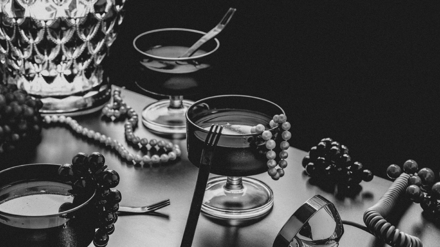 A vanity table holding cocktails, a pearl necklace and a vintage lamp.