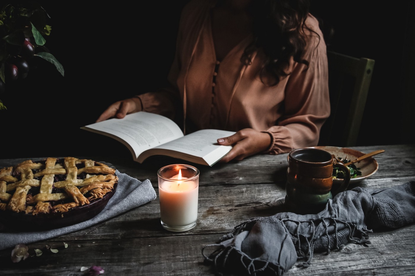 Dark lighting photo of a woman reading a book, with a lit candle and apple pie.