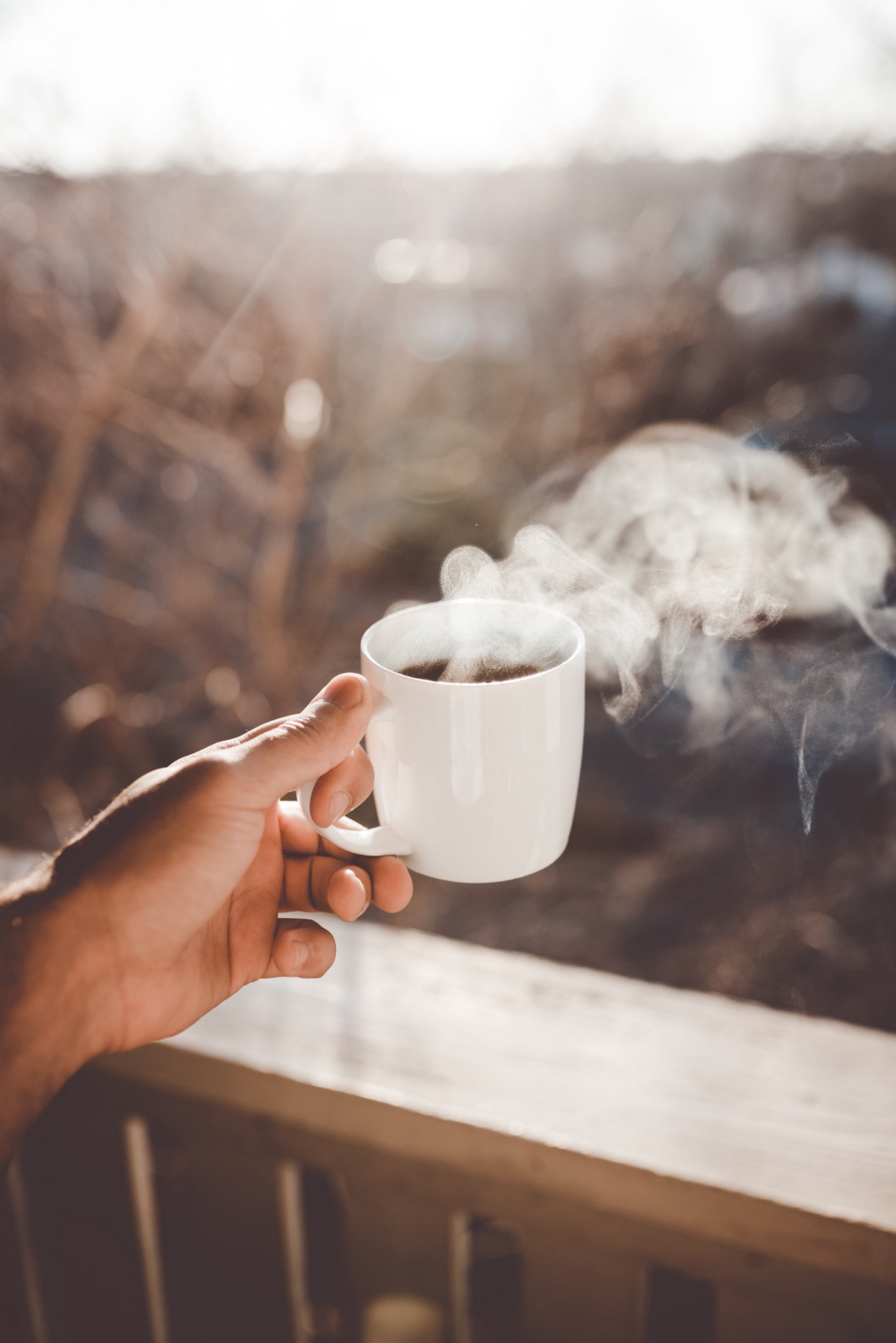 Outside on a porch, just a person's hand is in shot holding a steaming cup of coffee.