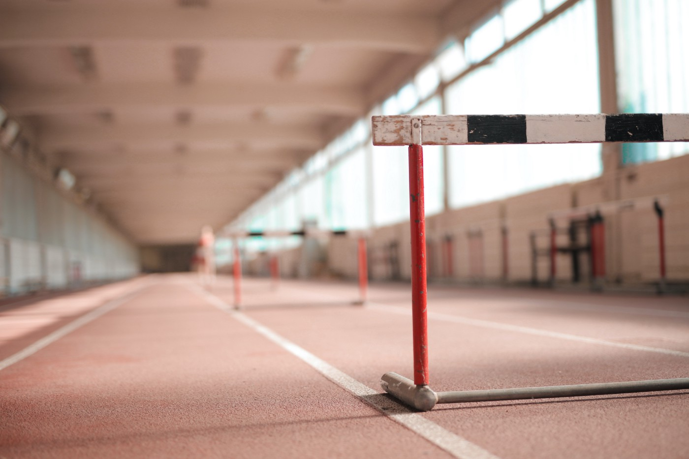 A brown indoor track is lit by daylight. In the foreground, a hurdle sits across one of the track lanes.