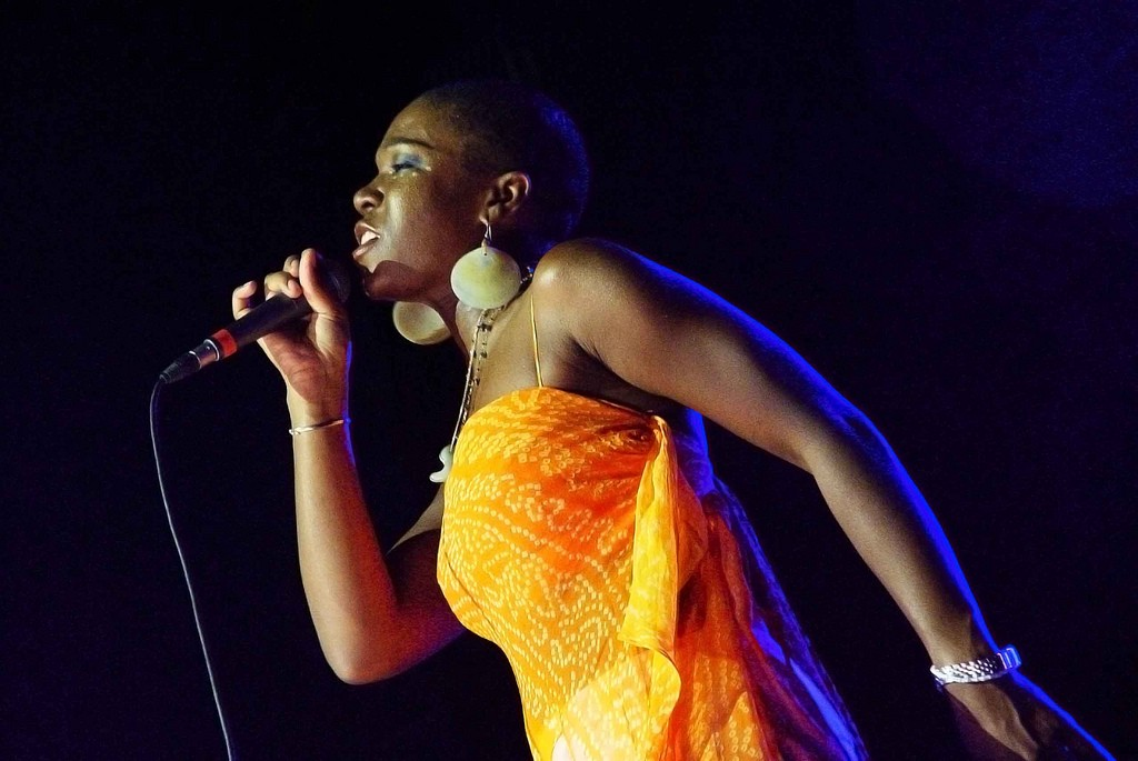 Photograph of singer India.Arie holding a microphone, singing. She's wearing an orange dress. The background is black.