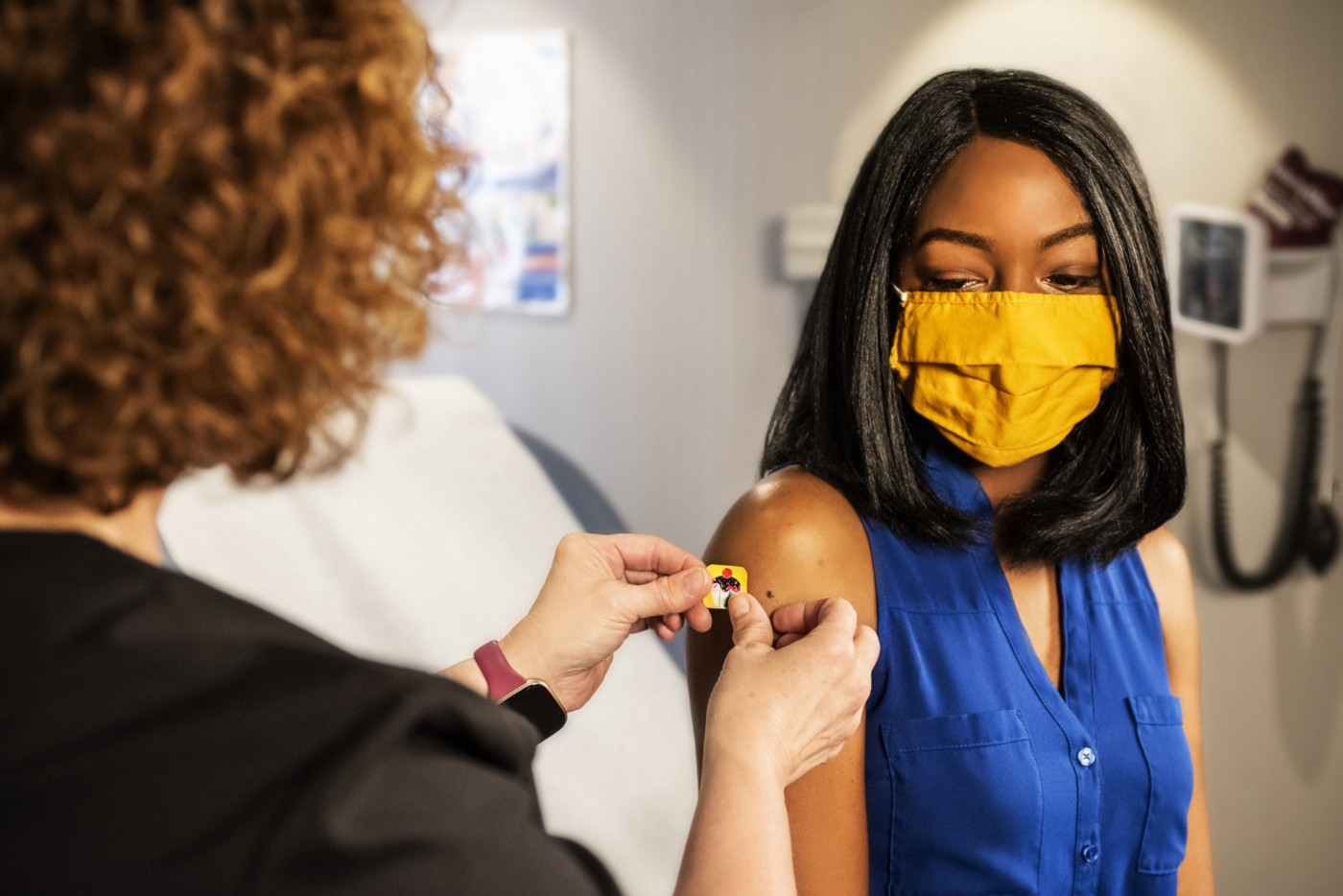 a Black woman wearing a blue sleeveless top receives a bandaid after receiving a vaccination from a white-appearing woman whose face is away from the camera