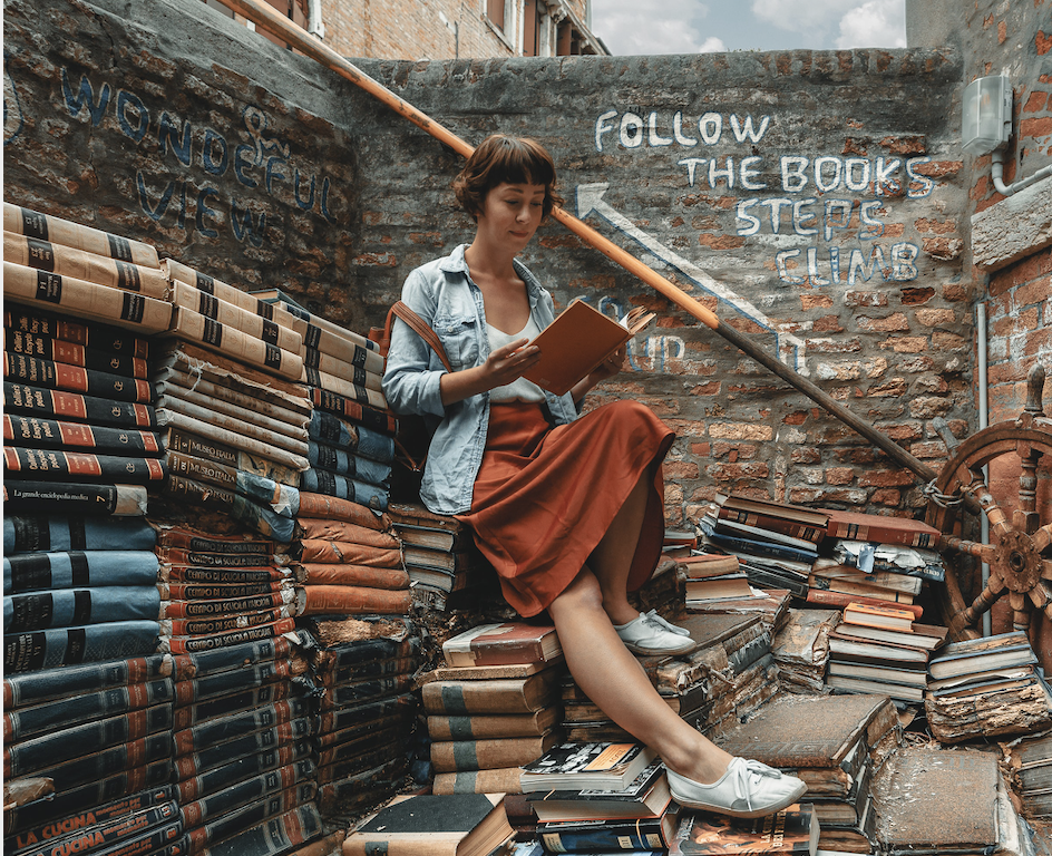 A woman reads a book will sitting on and around stacks of books.