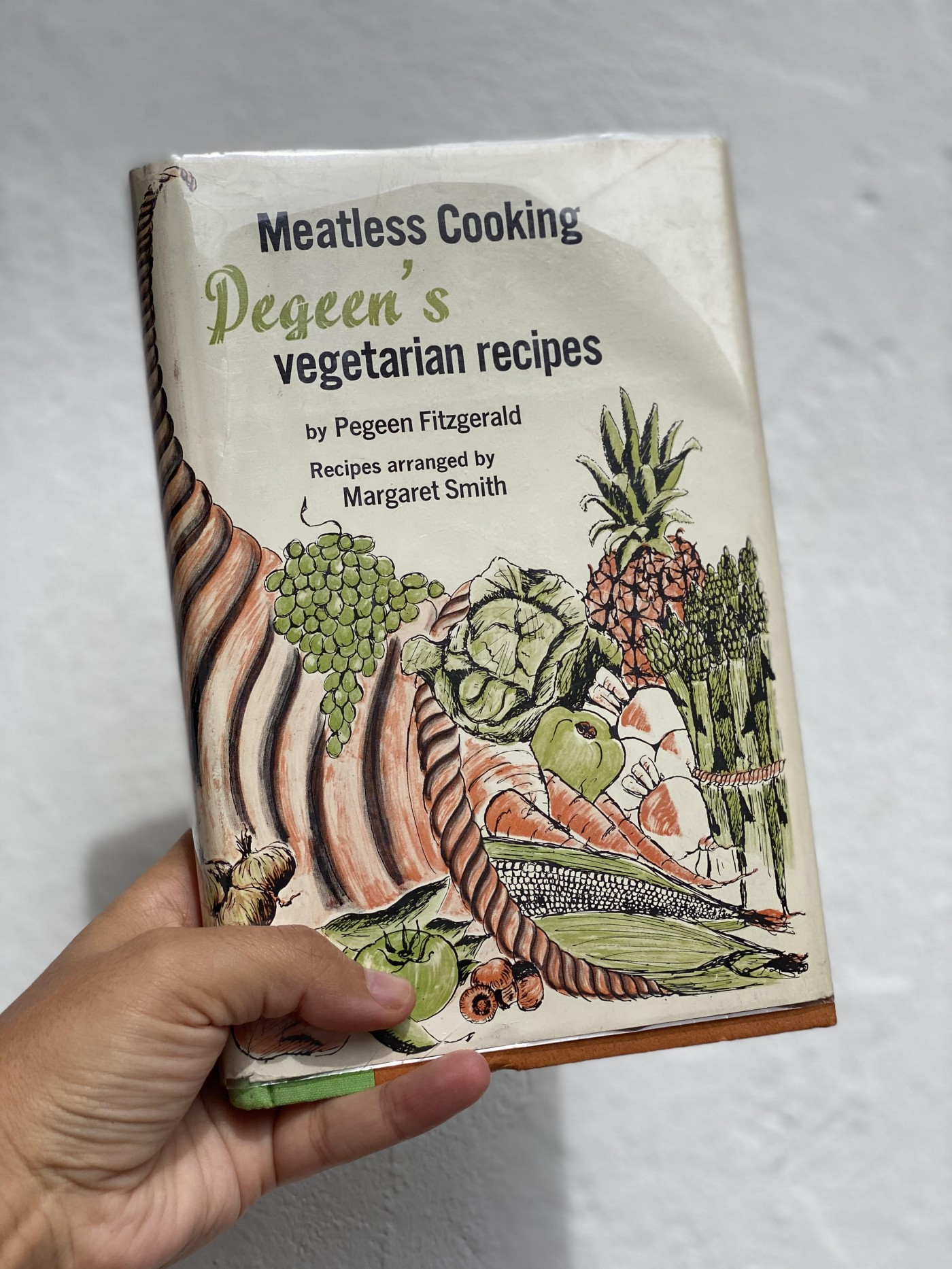 A hand holding up a vintage cookbook with a quaint illustration of fruits and veggies on the front.