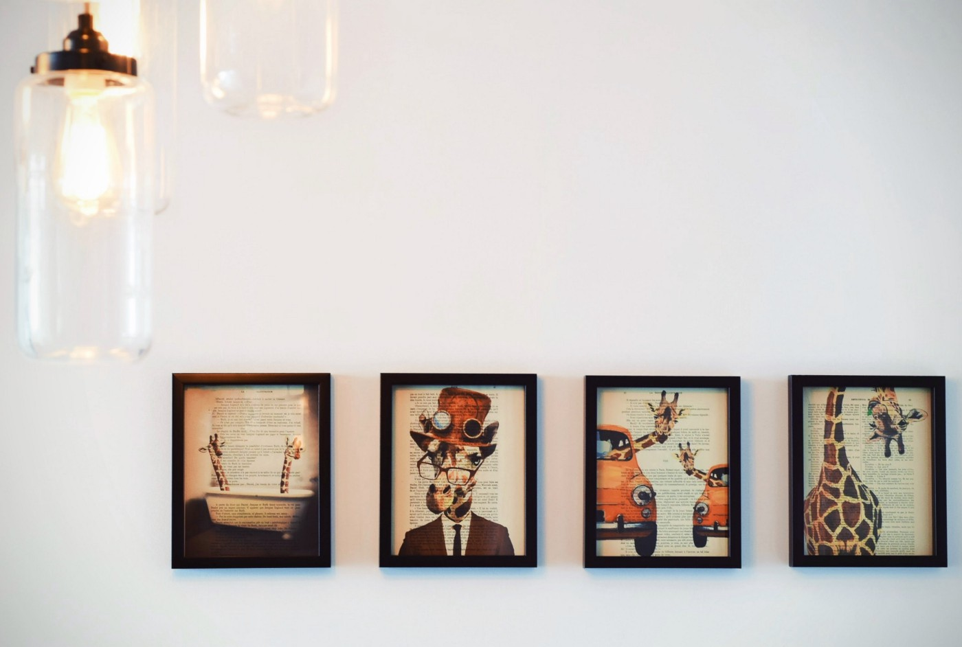 Four framed photos of illustrated giraffes on a white wall