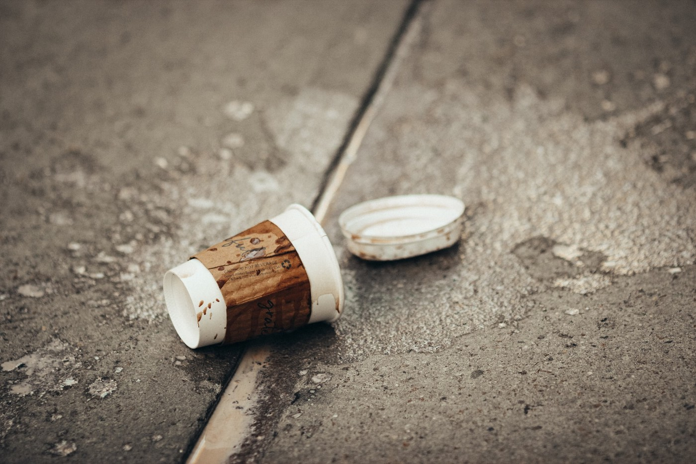 A tipped over coffee cup with the lid popped off on a sidewalk