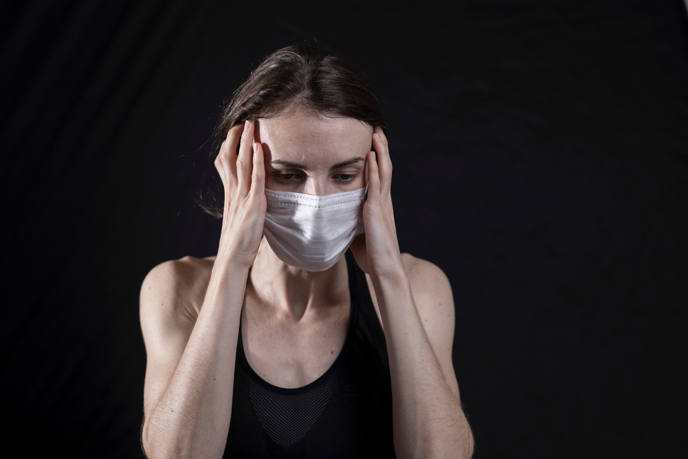 Woman in mask gripping her head in front of a black background.