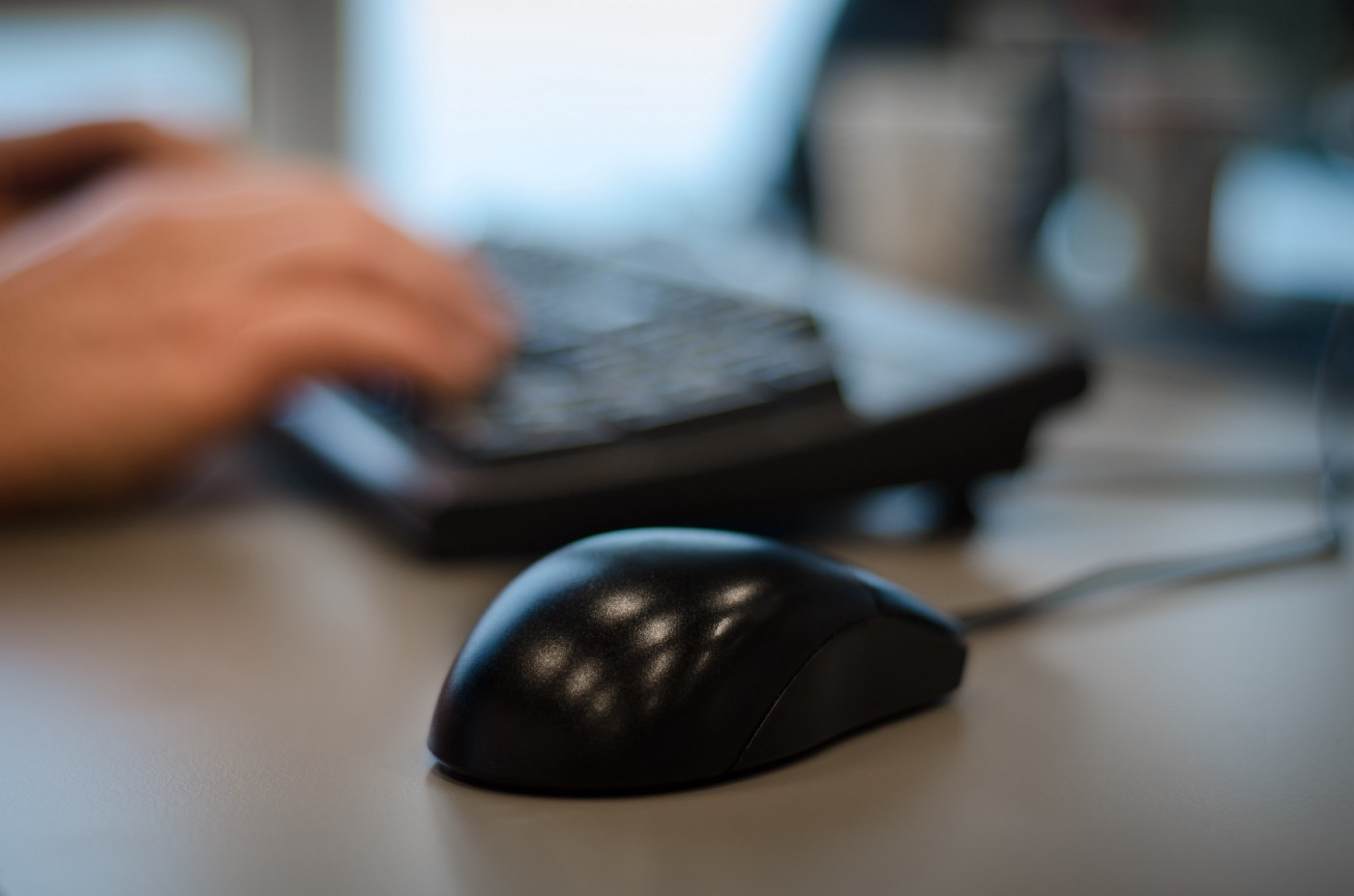 A computer mouse on a desk with hands on a keyboard slightly blurred in the background.