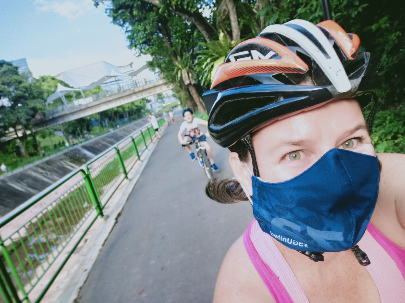 woman wearing a cycling helmet and face mask. She has green eyes and looks to be smiling under the mask. Behind her is an out of focus happy looking child on bicycle also wearing a helmet. They are on a cycle path with a bridge, buildings and trees in the background.