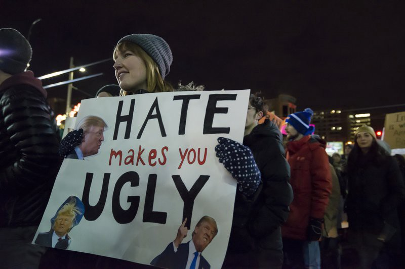 Protester with sign that reads Hate Makes You Ugly
