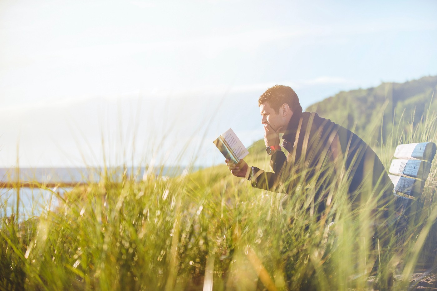 a man reads on a bench in nature