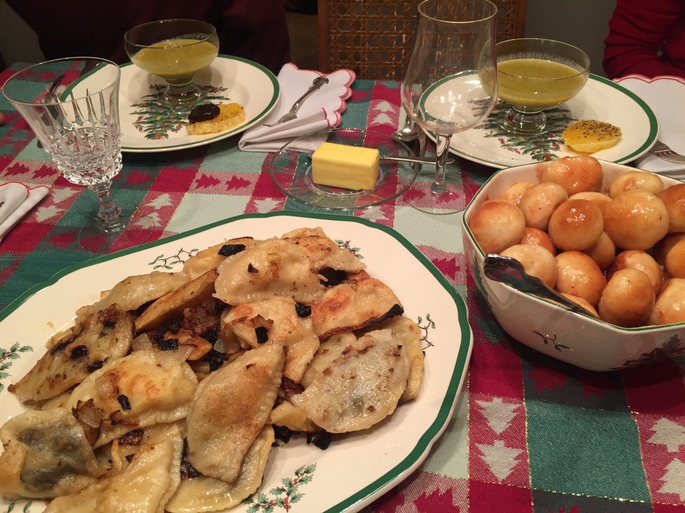 Plates with pierogi, bobalki, and glasses of pea soup sitting on top of a red, white, and green Christmas table cloth.