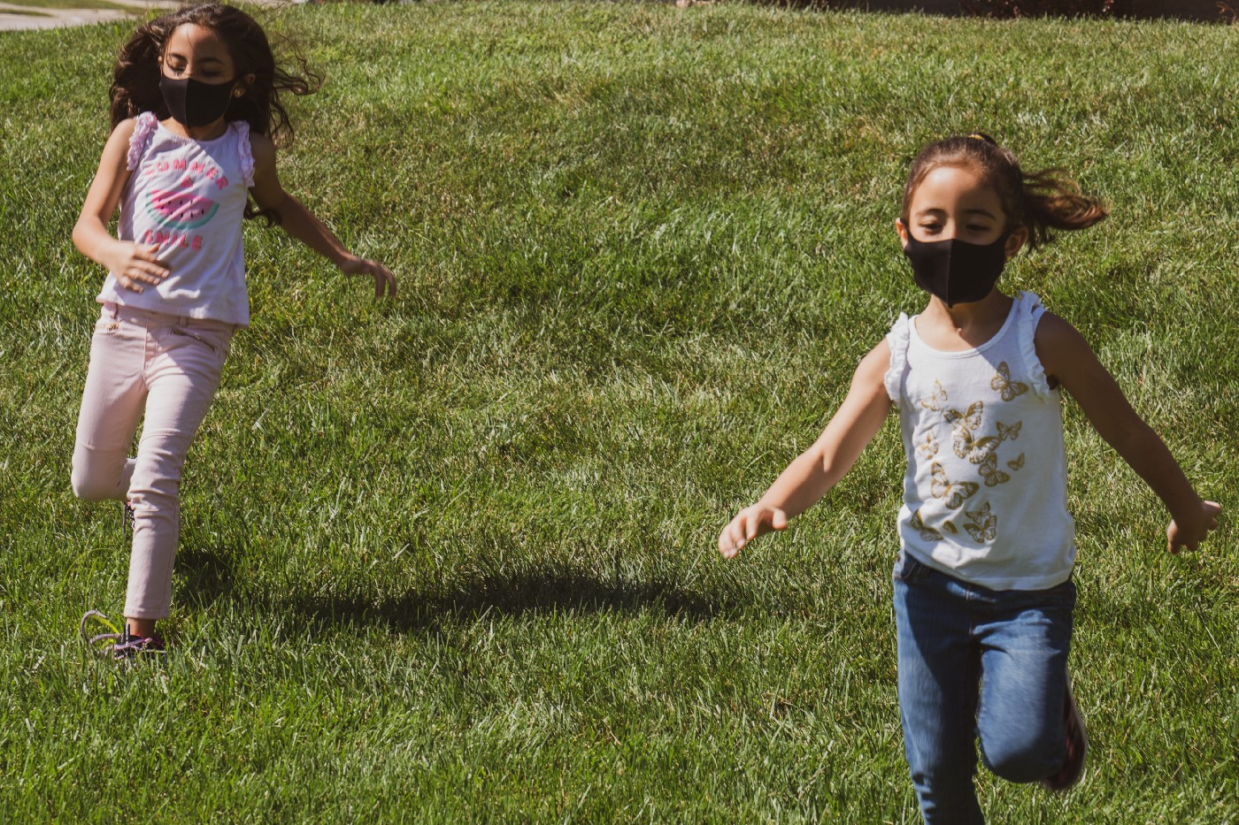 two girls wearing cloth face masks and playing on a green grass field during daytime