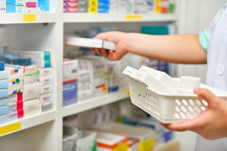 A photo of someone's torso and arms, picturing them moving medication between shelves.