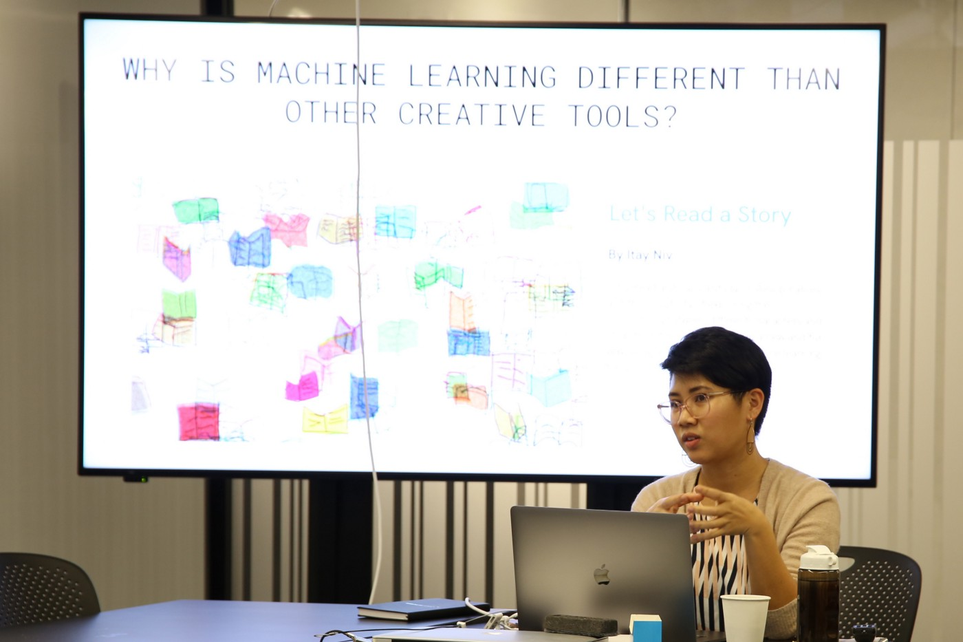 A woman sits in front of a screen giving a presentation about about ml5.js