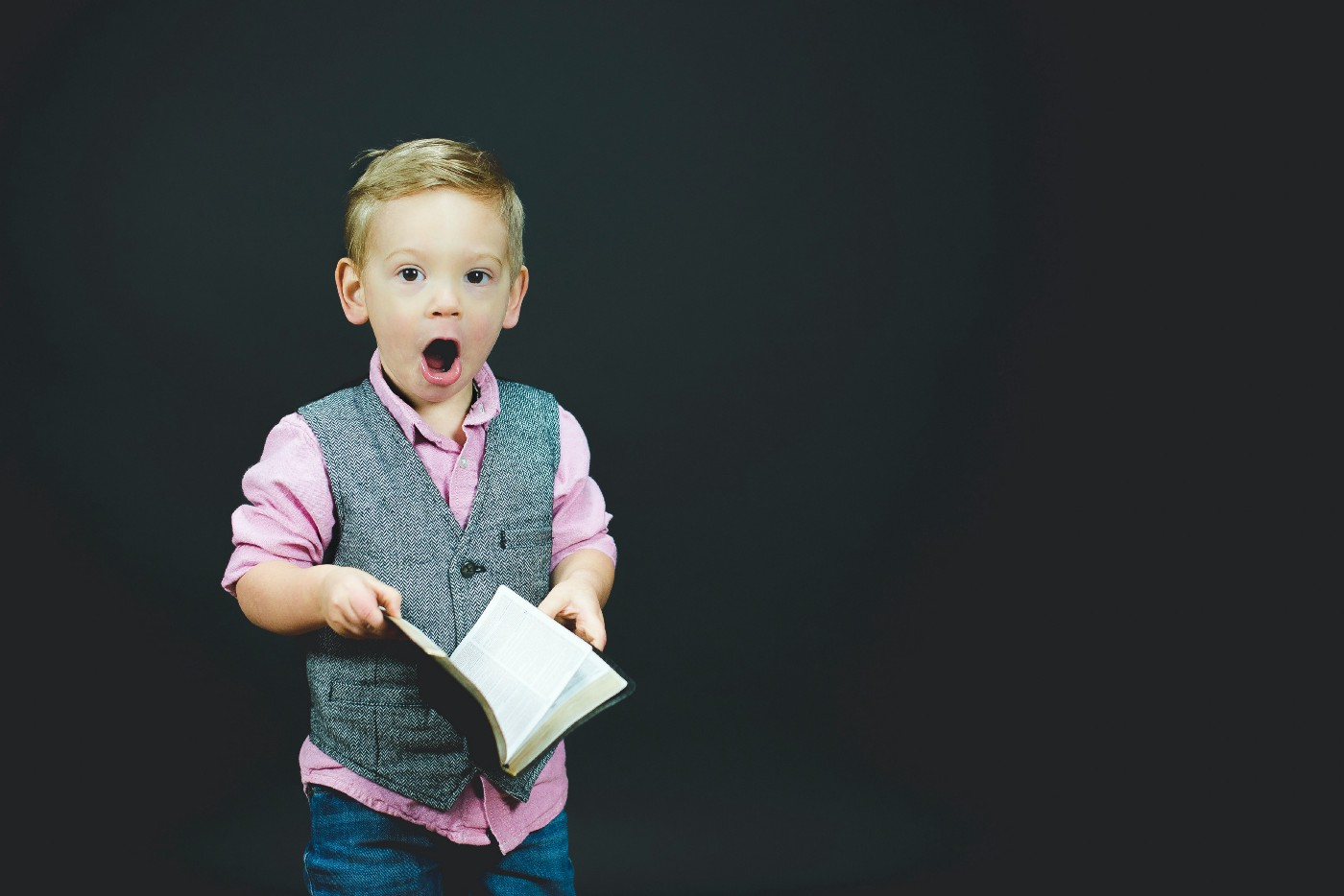 A little boy standing in front of black background dressed with a pick shirt, a gray best, and blue trouser. With a book opened in his hands, he looks at the camera like he is surprised — his eyes and mouth are open.
