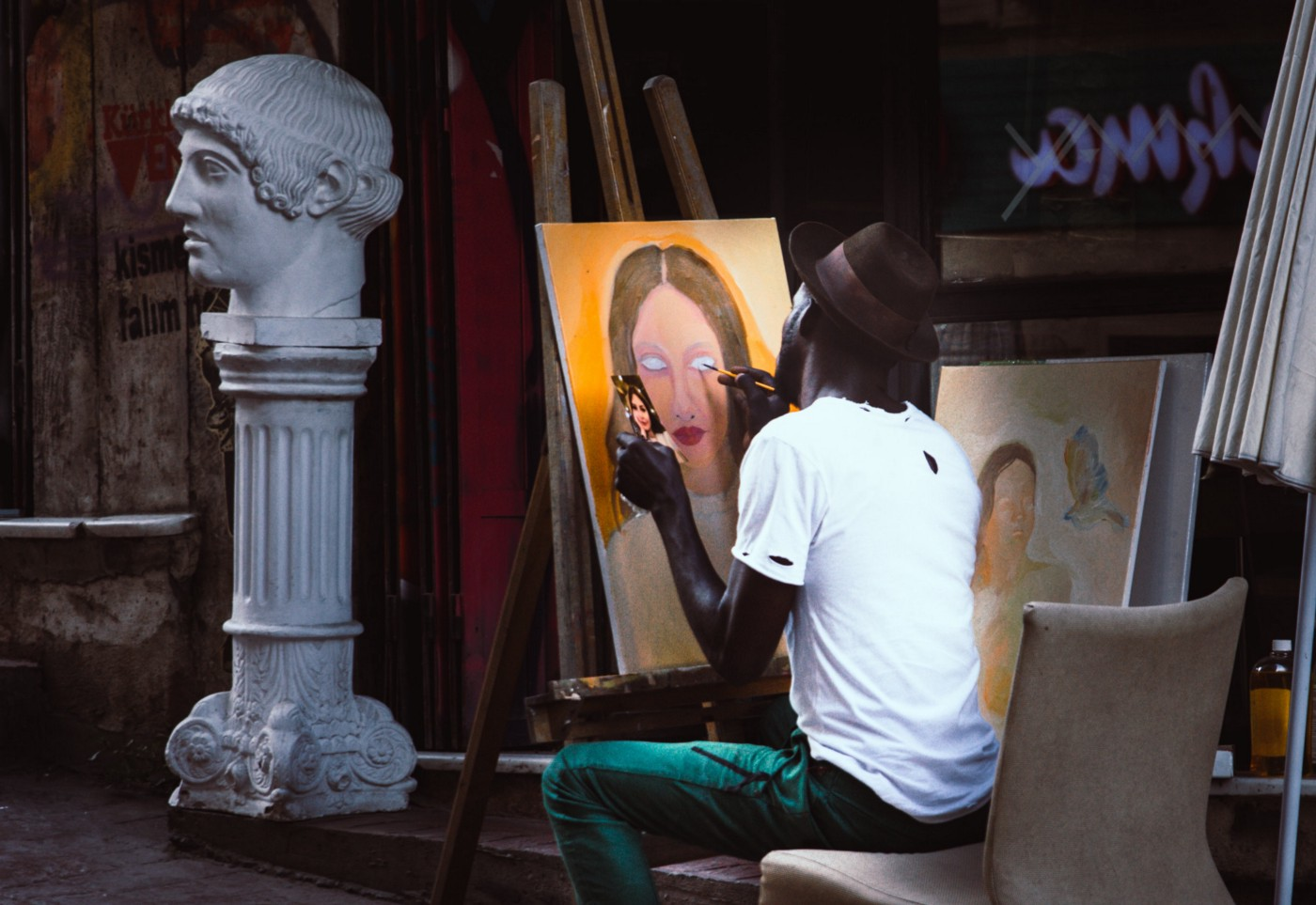 A Black man sits in a room painting a portrait of a woman. On the side of the room is a statue with a bust of a man on top of it.